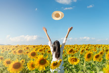 Happy Young And Long Hair Asian Woman In The Field Of Sunflowers, Standing Arm Raised Throwing Hats.