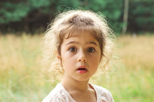 Close Up Portrait Of Beautiful Little Girl  Surprised With Something At Summer Day