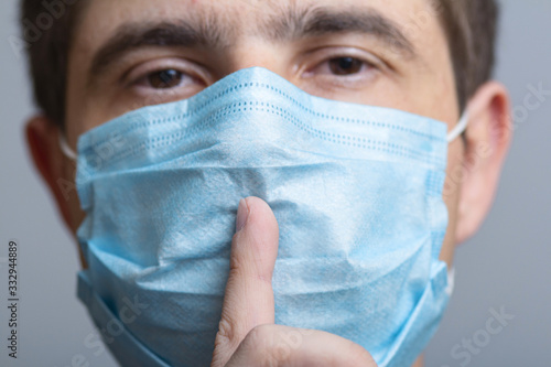 Photo portrait of a man in a protective medical mask on face showing sign of silence g
