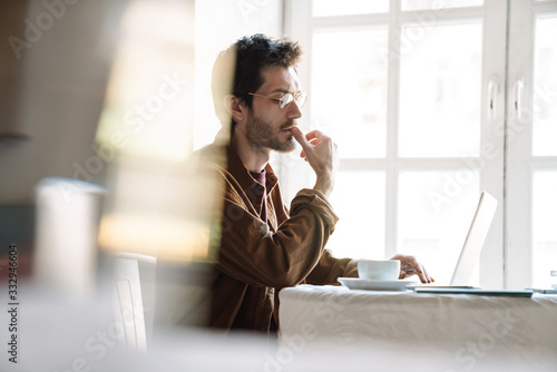 Canvastavla Image of handsome serious man using laptop while sitting