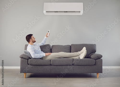 The young man turns on the air conditioner cools the air while sitting on the so Canvas Print