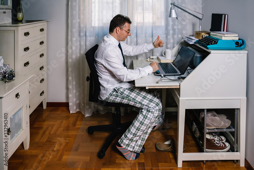Obraz Man working from home with laptop wearing shirt, tie and pajama pants - fototapety do salonu