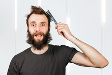 Young Bearded Overgrown Man Holding Comb And Combing His Hair. For Barbershop.
