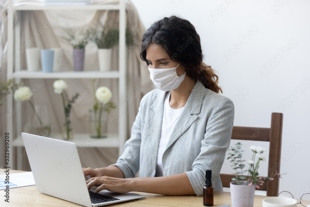 Fototapeta Young woman wear medical protective mask from corona virus pandemic work on laptop in office, female employee in face cover against covid-19 coronavirus epidemic use computer at workplace