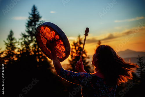 Foto beautiful shamanic girl playing on shaman frame drum in the nature