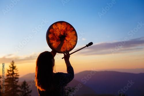 beautiful shamanic girl playing on shaman frame drum in the nature Fototapete