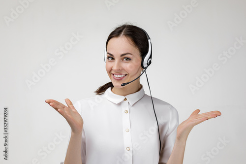 Obraz Beautiful smiling woman consultant of call center in headphones on gray background. female customer support operator with headset - fototapety do salonu