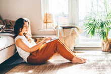Young Woman Working From Home. Girl Using Laptop At Sunny Room.