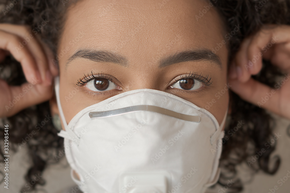 Fototapeta Closeup of adult african american woman putting mask on her face. Action to prevent the spread of the virus by infected people. Coronavirus or Covid-19 quarantine