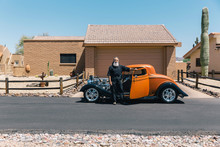 Cool Man Standing Near His Hot Rod Outside Of His Home