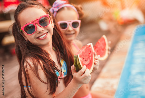 Happy sisters eating watermelon on poolside Tablou Canvas