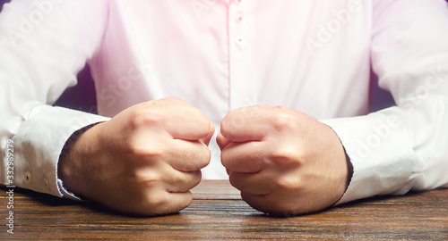 Photo A man holds his closed fists on the table