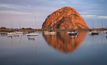 Morro Rock Reflects In The Waters Of Morro Bay As Boats Are Mored In Still Waters