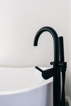Close Up On A A Black Faucet Filling Up A Bathtub