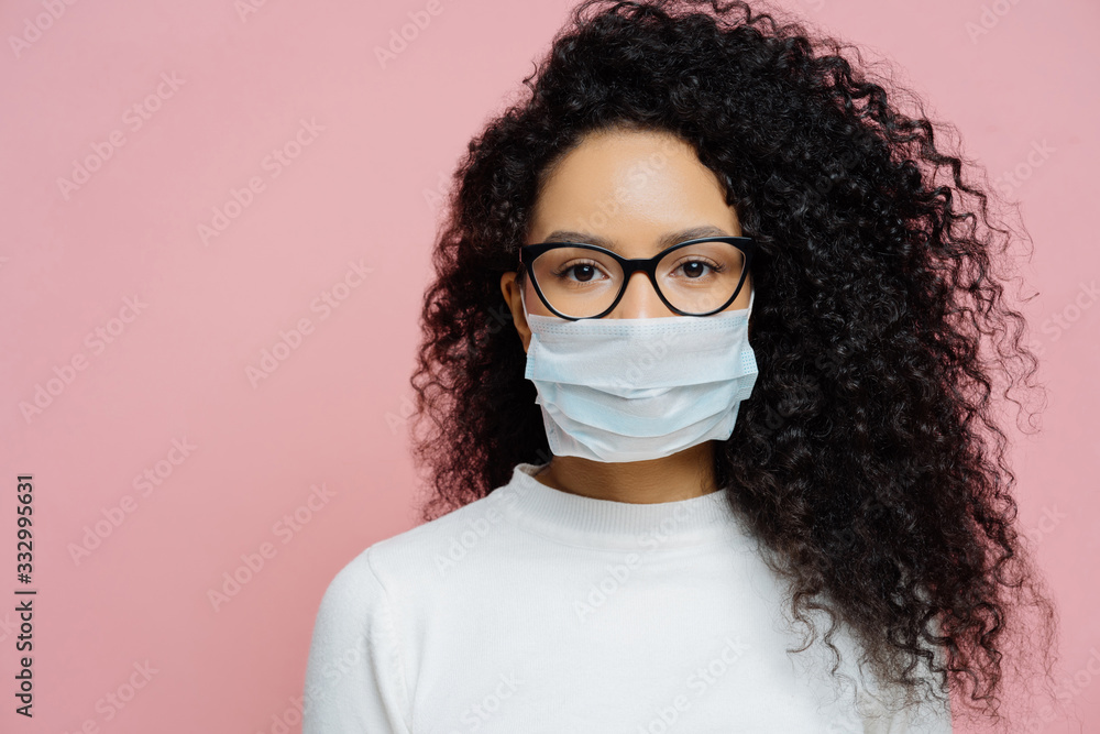 Fototapeta Covid-19, infectious virus. Close up shot of young woman with curly bushy hair, wears transparent glasses and medical disposable mask, cares about her health, protects in dangerious situation