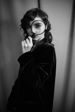 Portrait Of Young Woman In Jacket Looking Through Magnifying Glass