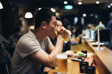 Portrait of man drinking beer in pub