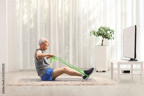 Fotografía Senior man exercising with an elastic band in front of a tv at home