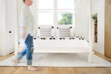 Woman Walking Through Modern Design Farmhouse Bedroom