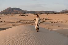 Woman In Beige Trench Coat Walking In Desert.