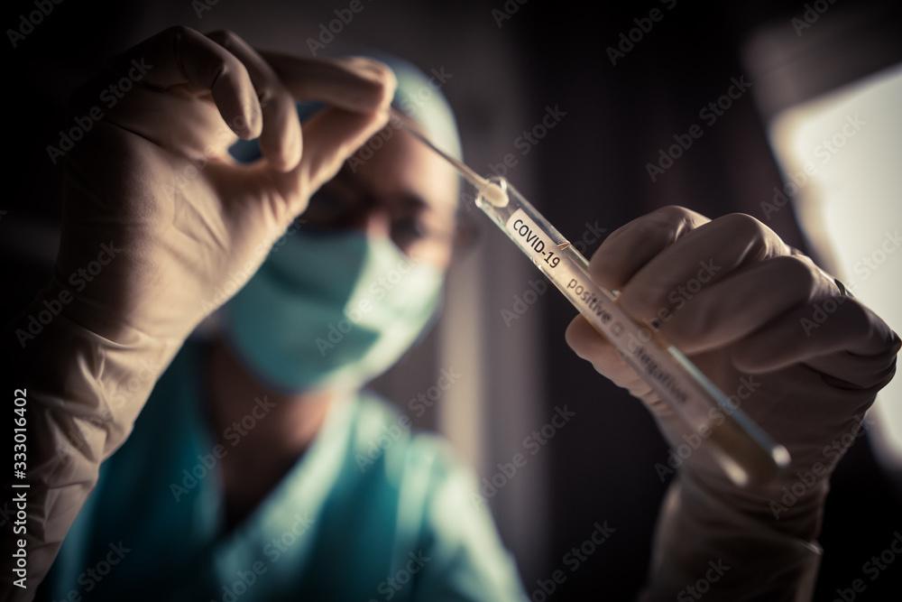 Fototapeta Doctor holding a coronavirus COVID-19 test tube