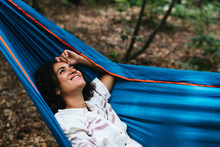 Portrait Of A Woman Laughing So Relax In A Blue Hammock In The Forest.