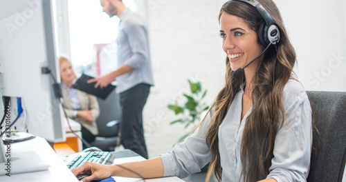 Obraz Friendly young woman call center operator with headset using computer at office - fototapety do salonu