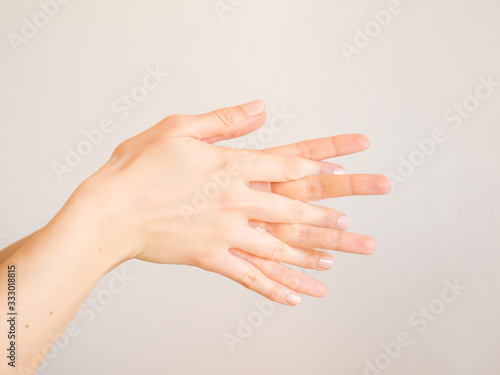 Female hands cleaning washing with sanitizer gel over bright gray background Slika na platnu