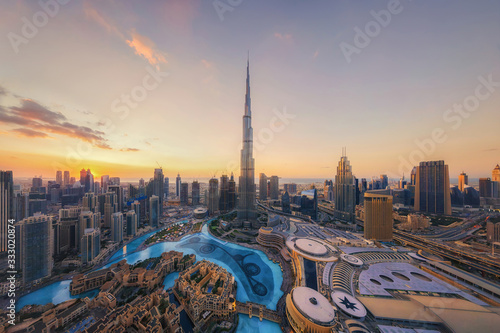 Fototapeta Aerial view of Burj Khalifa in Dubai Downtown skyline and fountain, United Arab Emirates or UAE. Financial district and business area in smart urban city. Skyscraper and high-rise buildings at sunset. obraz