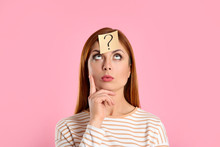 Emotional Woman With Question Mark Sticker On Forehead Against Pink Background