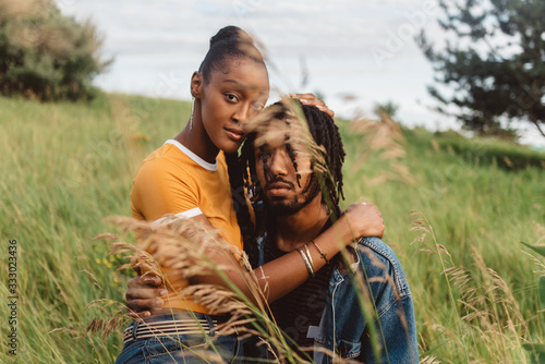 A young engaged african american couple posing for pictures in a meadow - 333023436
