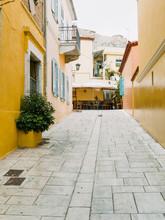 Alleyway Between Yellow Buildings With Doors And Balconys In Athens Greece