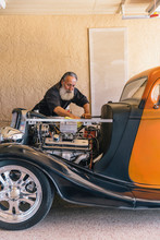 Mechanic With Beard Working On Hot Rod Car In Home Workshop