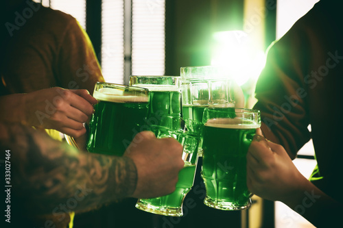 Obraz Group of friends toasting with green beer in pub, closeup. St. Patrick's Day celebration - fototapety do salonu