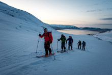 A Group Of Skiers Skiing At Sunrise In Iceland With Water Behind