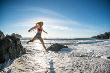 Teenage Girl Jumping Off Rock Into Surf At Beach