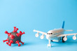 Travel restrictions concept made of coronavirus cell and airplane toy on pastel blue background.