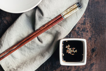 Soy Sauce And Sesame In A Vessel And Bamboo Chopsticks