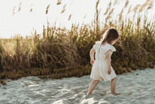 Behind View Of Young Toddler Girl Walking At Sandy Beach During Sunset