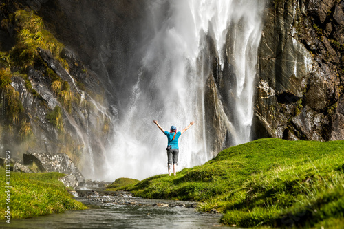 Figure standing in front of waterfall spray, in green nature landscape - 333033629