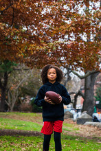 Portrait Of Confident Girl Practicing American Football At Park In City