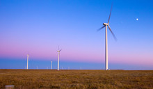 Wind Turbines In Field Against Blue Sky With Moon