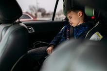 Boy Sleeping In Car Seat In Ca...