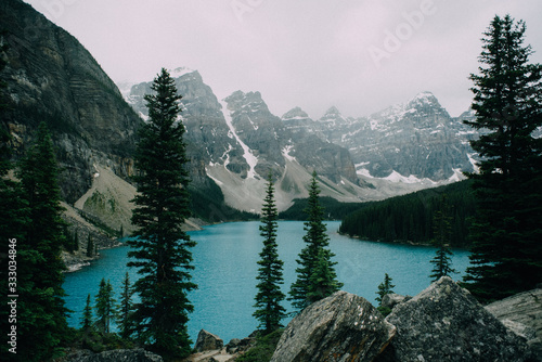 crystal clear blue lake sits at the base of mountains with trees - 333034846