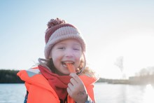 Portrait Of A Young Girl With A Life Jacket On Blowing A Whistle