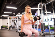 A Blonde Woman Doing Bicep Cur...