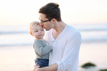 A Young Father Giving His Son A Kiss On The Temple At The Beach.