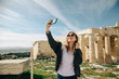 Smiling female tourist make selfie in front of Parthenon Temple at the Acropolis of Athens