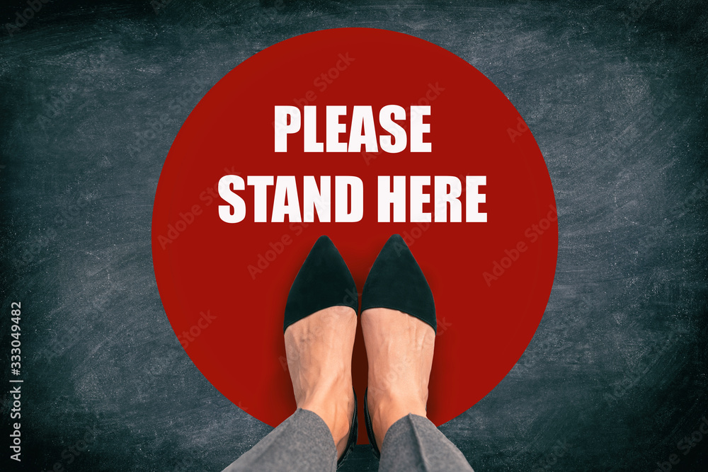 Fototapeta COVID-19 Coronavirus message asking supermarket customer to stand in space. Top view of feet standing in red circle with text in public space practicing social distancing. Blackboard background.