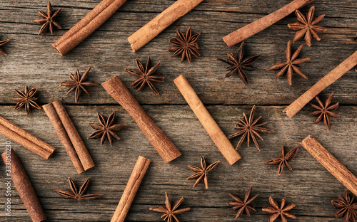 Photo brown cinnamon sticks and dry star anise on a gray wooden background